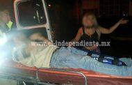 Pareja lesionada al impactar su motocicleta contra un taxi